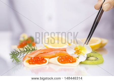 Salmon and red caviar on a plate with fruits. Chef decorate the dish, he puts forceps flower.
