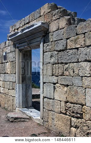 old ruined ancient Greek door portal in wall of limestone blocks on blue sea background