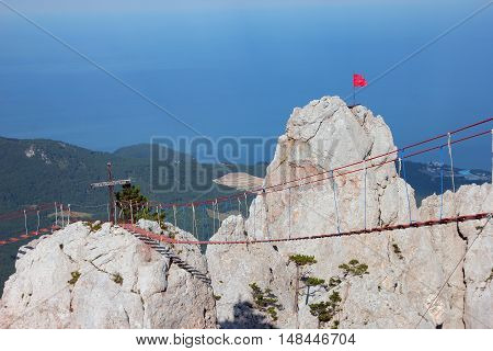 hanging bridge on the rocky mountain tops with red flag on top in Crimea