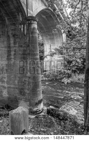 The Tumwater River flows beneath a bridge. Black and white image.