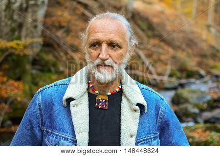 Good looking elderly man outdoors walking along mountain creek through colorful autumn forest