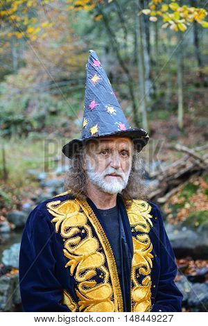 Portrait of old mysterious wizard having a rest in deep autumn forest