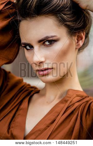 Attractive young girl with long hair wearing casual clothes posing on a background of shops showcases