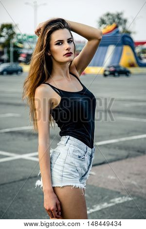 Attractive young girl with long hair wearing body posing in urban area