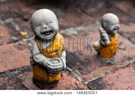 Monks with bowls - Ancient statuette at the temple in Ayuttaya Thailand