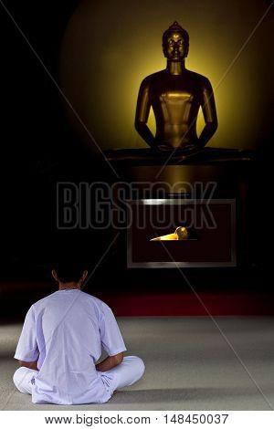 PATHUM TANI, THAILAND - DECEMBER 31, 2012: Pilgrim meditate in front of Buddha statue at Dhammakaya Meditation Center