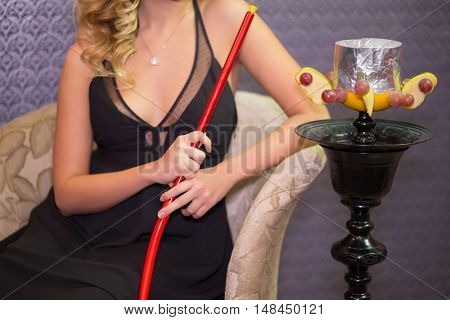 Beautiful girl in black dress with decollete in the hookah room, focus on the hookah.