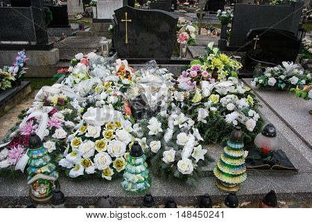 Graves, Tombstones And Crucifixes On Traditional Cemetery. Votive Candles Lantern And Flowers On Tom