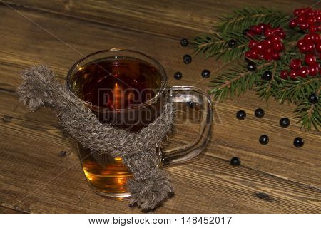 Cup of black tea in the scarf and the Rowan berries with spruce branches
