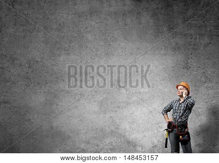 Engineer woman talking mobile phone against concrete wall background