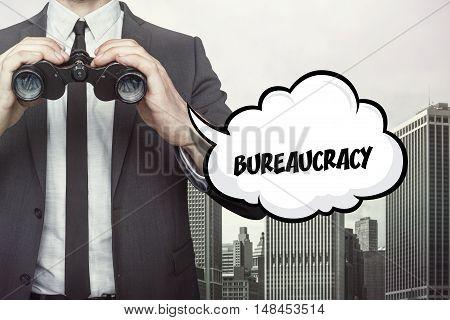 Bureaucracy text on  blackboard with businessman and key