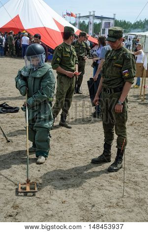 Tyumen, Russia - June 11, 2016: Race of Heroes project on the ground of the highest military and engineering school. Exhibition of weapon. Boy tries on sapper suit