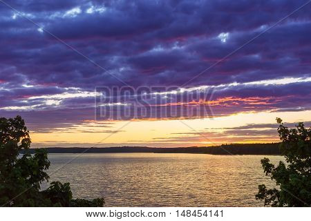 Vyborg. Bright summer sunset over Gulf of Vyborg. Evening calm in sea Bay Leningrad region Saint-Petersburg Russia. Sun disappears behind the forest and reflected in water and clouds