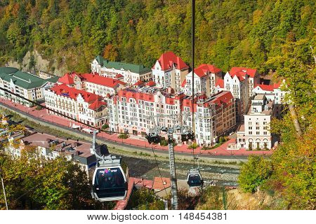 SOCHI RUSSIA - OCTOBER 31 2015: mountain zipline through autumn forest on backdrop of Rosa Khutor funicular railway to observation deck tops 2320 m. Krasnaya Polyana - Alpine ski resort constructed from 2003 to 2011 for Sochi Olympic games. Russia