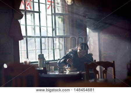NGARI, TIBET - MAY 2, 2013: Chinese young man eating in dinner room of monastery guesthouse.