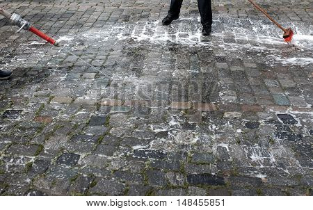 Cleaning of cobblestone street with water hose and broom