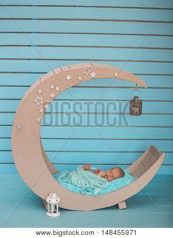 Studio portrait of newborn baby boy sleeping in moon bed.