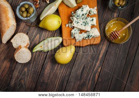 Blue cheese with honey, olive and pears on rustic table.