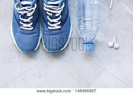 Flat lay sport shoes bottle of water and earphones on gray concrete background. Concept healthy lifestyle sport and diet. Focus is only on the sneakers.