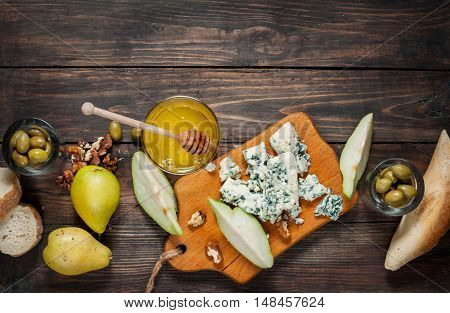 Blue cheese with honey, olive and pears on rustic table. Text place.