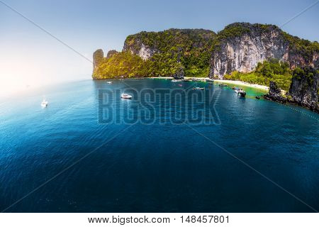 Aerial view of the sea with rocky island and anchored yacht in the bay.