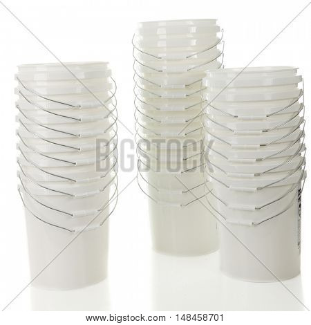 Three tall stacks of white, plastic buckets.  On a white background.