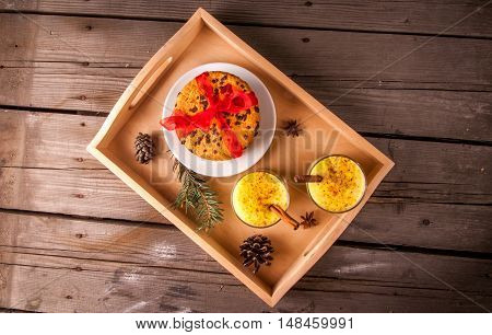 Traditional Christmas drink eggnog and cookies on a wooden background surrounded by Christmas tree branches, top view, copy space