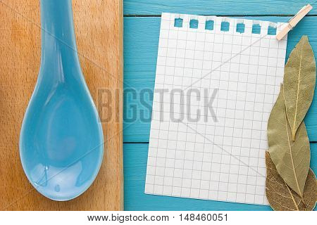 For recording cooking recipes and kitchens. A piece of paper with a pin on turquoise yellow-blue wooden Board and clay spoon