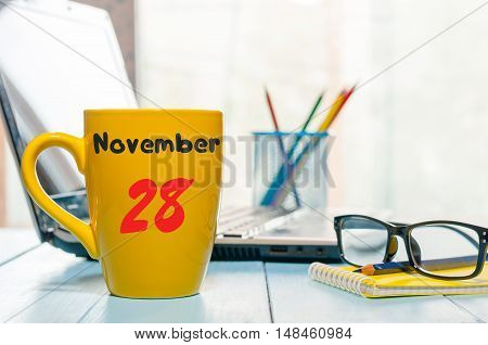 November 28th. Day 28 of month, morning coffee cup with calendar on financial adviser workplace background. Autumn time. Empty space for text.