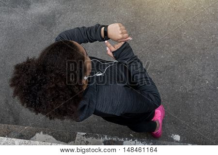 Young African American woman checks activity tracker during outdoor exercise