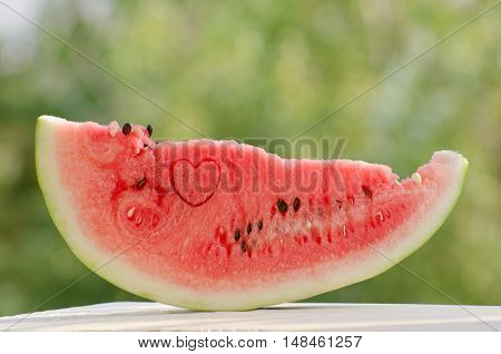Large slice of watermelon on a green background with a heart in the flesh