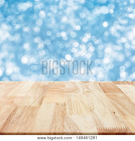 Modern wood table with blue blurry background for display your product.