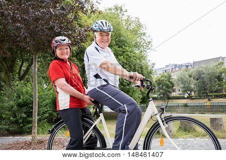 Portrait Of Smiling Senior Couple Riding Bicycle