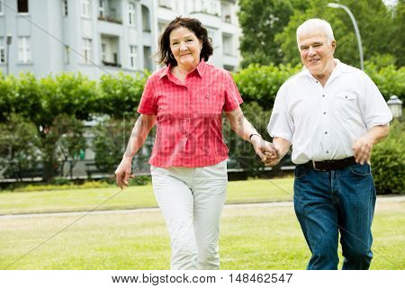 Happy Senior Couple Running In Park Holding Hands