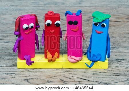 Children creativity. Figures dads moms and daughters made of wooden bars and plasticine lying on a wood table
