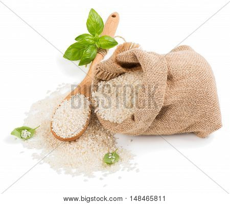White round rice sprinkled from burlap sack with wooden spoon isolated on a white background.