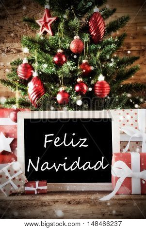 Christmas Card For Seasons Greetings. Christmas Tree With Balls. Gifts Or Presents In The Front Of Wooden Background. Chalkboard With Spanish Text Feliz Navidad Means Merry Christmas