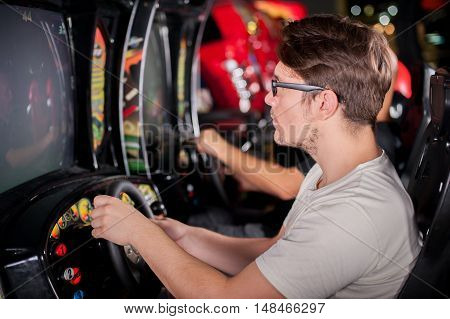 Young man playing driving wheel video game in game room