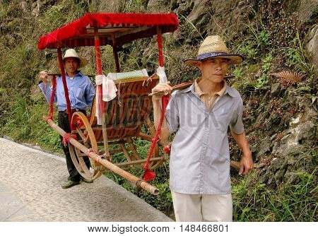 Longsheng China - May 2 2006: Porters use covered sedan chairs to transport tourists down a mountainside from Ping-An Village