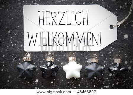 Label With German Text Herzlich Willkommen Means Welcome. Black And White Christmas Tree Balls On Black Paper Background With Snowflakes. Christmas Decoration Or Texture. Flat Lay View