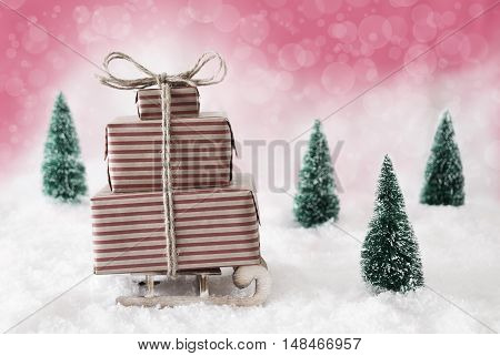 Sleigh With Christmas Gifts Or Presents. Snowy Scenery With Snow And Trees. Pink Background With Bokeh Effect.