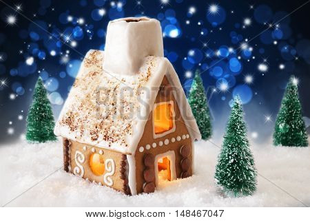 Gingerbread House In Snowy Scenery As Christmas Decoration. Christmas Trees And Candlelight For Romantic Atmosphere By Night. Dark Blue Background With Bokeh Effect And Sparkling Stars.