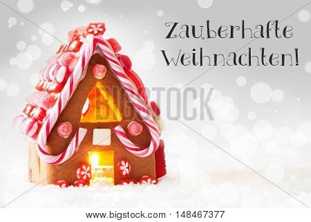 Gingerbread House In Snowy Scenery As Christmas Decoration. Candlelight For Romantic Atmosphere. Silver Background With Bokeh Effect. German Text Frohe Weihnachten Means Merry Christmas