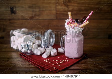 Glass jar of homemade raspberry smoothie cocktail, served with whipped cream, caramel jelly beans and wafer rolls over old dark wood background with jar of marshmallow over background.