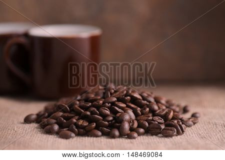 Marco shot of dark rich roasted coffee beans with coffee cups window light copy space and room for text over blurred lower part ideal for pinterest or blogs