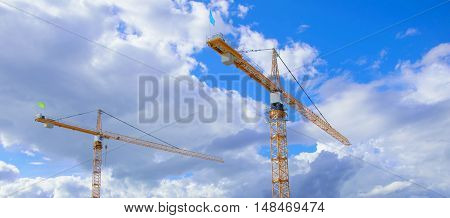 two tall construction crane at a construction site