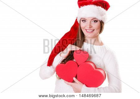 Christmas winter happiness concept. Woman wearing santa helper hat holding many red heart shaped gift boxes isolated on white