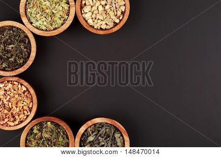 Assortment of dry tea in little bowls, forming frame on black background. Green and black tea, mint, melissa, ginger, apple, lime tree and other components for perfect beverage.