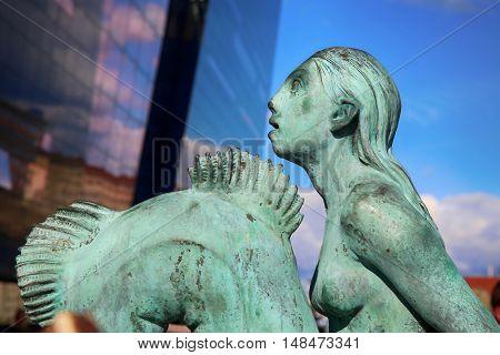 Mermaid statue in front of the main harbour The Black Diamond The Copenhagen Royal Library (Det Kongelige Bibliotek) in Copenhagen Denmark