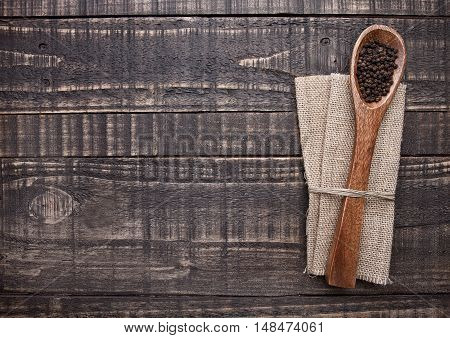 Pepper on spoon and kitchen towel on wooden board. Place for text